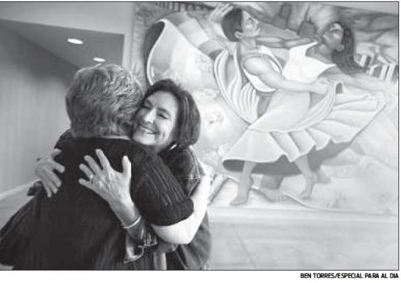 """Anita Marcos (izq.) abraza a Nora de Hoyos Comstock, la fundadora del grupo de apoyo a mujeres Las Comadres para las Américas, durante la presentación del libro """"Count on Me"""", en Dallas."""